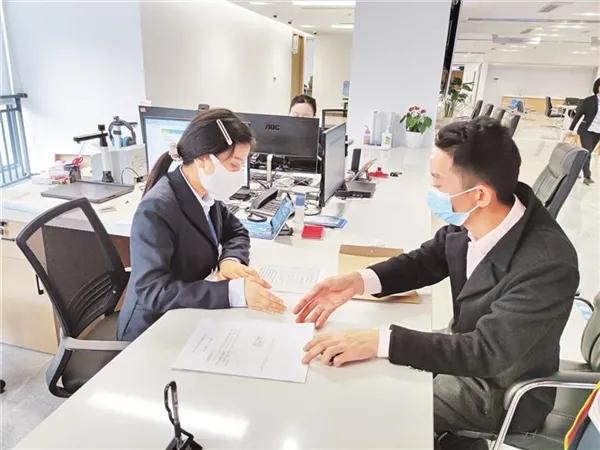 白云区政务服务中心工作人员正在审核办理营业执照
